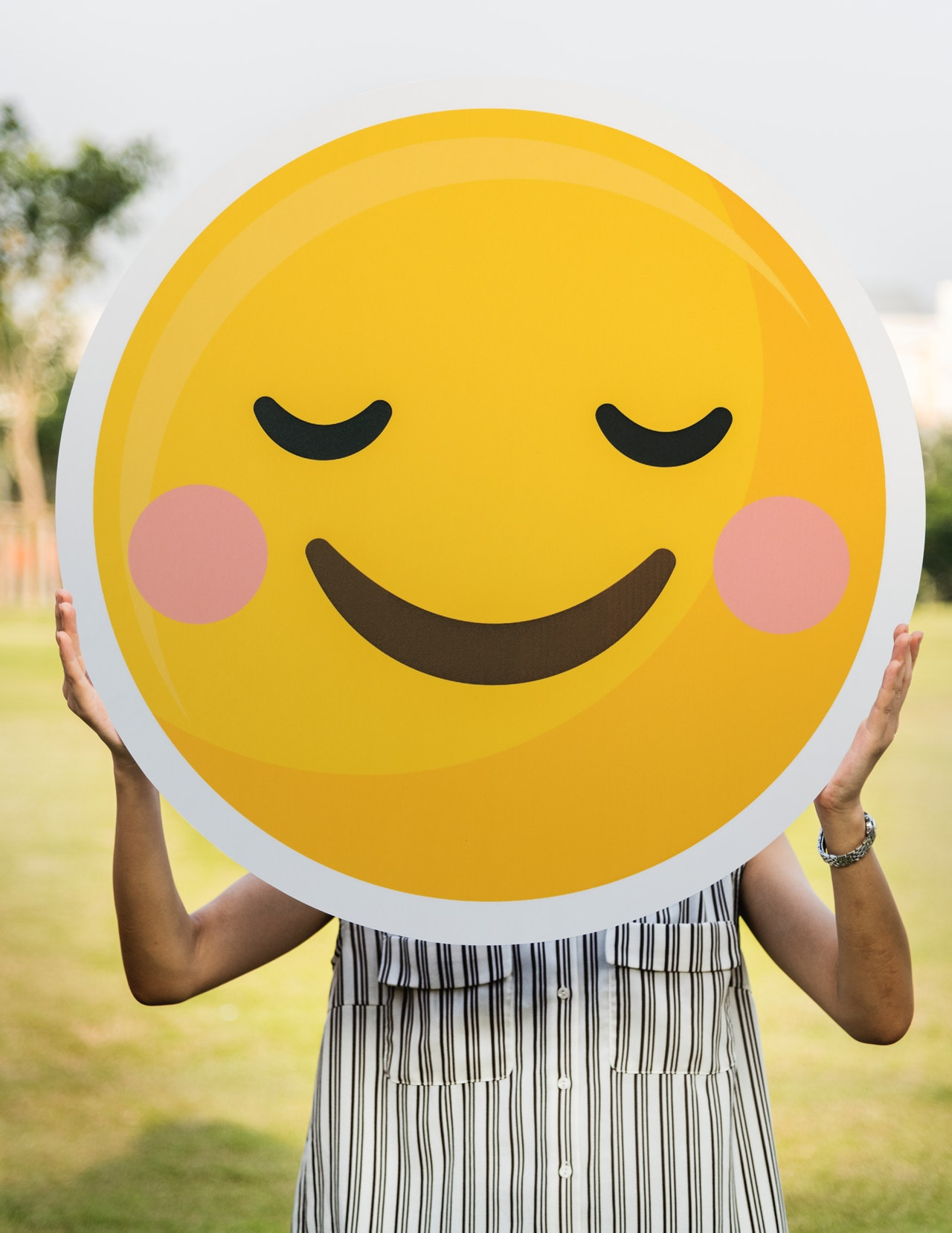 Person holding a large smiley face illustration.