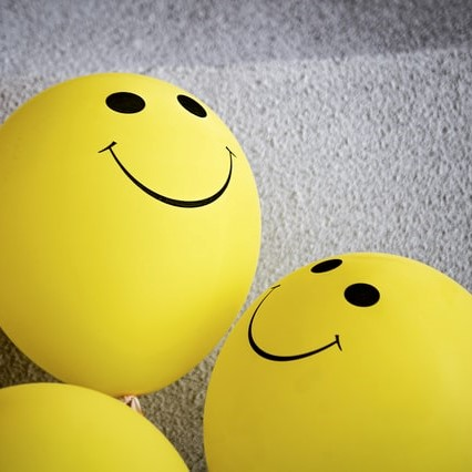 Yellow balloons with smiley faces on them.