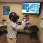 Center for New Media Design student worker, Terry, playing a soccer game in the VR Lab.